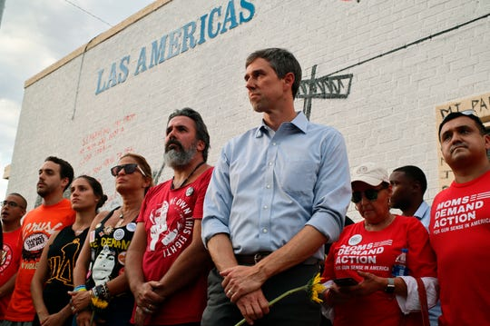 Muralist Manuel Oliver, whose son was killed in the Parkland, Florida, shooting, at center in red, is flanked by his wife and daughter, left, in black, and Democratic presidential candidate Beto O'Rourke, right in blue, during an unveiling ceremony for Oliver's mural, in El Paso, Texas, on Sunday, Aug. 4, 2019. The mural, which advocates for humane treatment of immigrants, became a memorial after 20 people were killed Saturday in an attack that officials are investigating as a hate crime. The death toll rose to 22 on Monday, Aug. 5, 2019.