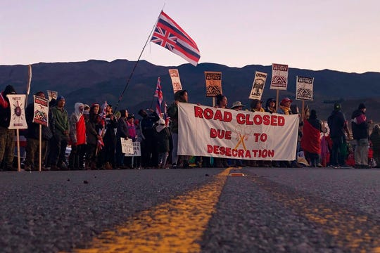 In this July 15, 2019 file photo, demonstrators block a road at the base of Hawaii's tallest mountain, in Mauna Kea, Hawaii, to protest the construction of a giant telescope on land that some Native Hawaiians consider sacred.