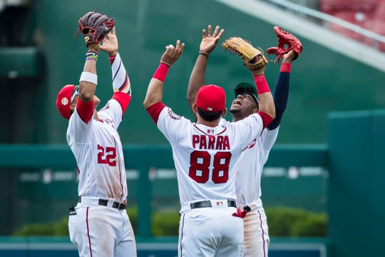 Outfielders Juan Soto, Gerardo Parra and Victor Robles celebrate a win.
