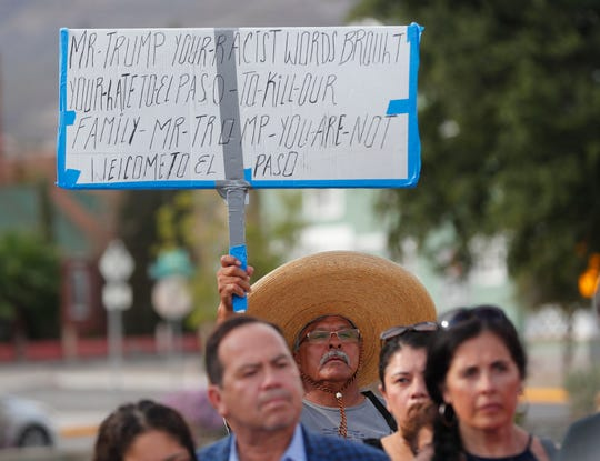 A man holds a sign directed at President Trump before a march at Houston Park in El Paso on Aug. 4, 2019.
