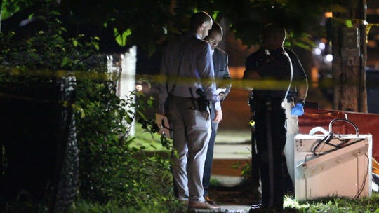 Neptune Township police officers and Monmouth County Prosecutors Office detectives confer at the scene of a multiple shooting on Sewall Avenue late Monday night, August 5, 2019.