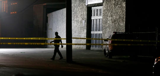 A Neptune Township police officer walks through the scene of a multiple shooting on Sewall Avenue late Monday night, August 5, 2019.