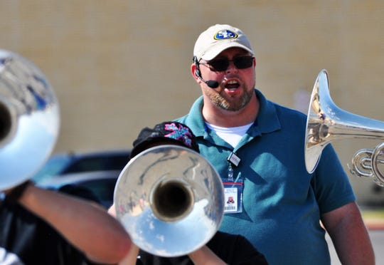 French horn players march by Matthew Raines, new Cooper High School director of bands, during marching band camp at the school campus on Tuesday.