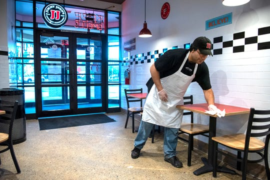 Arash Keshavarz cleans tables during the first day of business at the new Jimmy John's on Tuesday, Aug. 6, 2019 in Battle Creek, Mich.