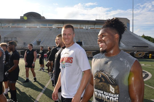Western Michigan quarterback Jon Wassink (left) laughs about throwing a jump ball to receiver D'Wayne Eskridge during captains practice at Waldo Stadium in Kalamazoo on Monday, July 29, 2019.
