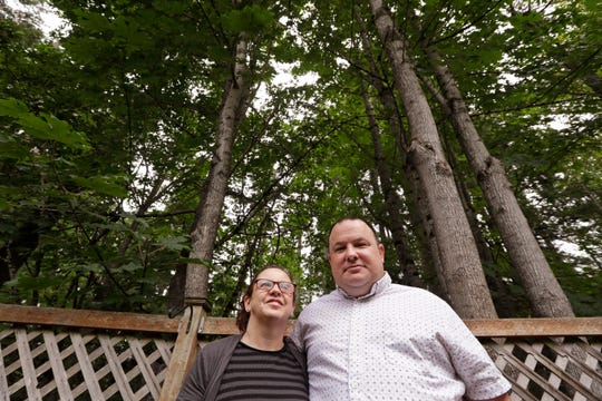 Amy and Jason Ritchie stand in the backyard of their home, adjacent to a forest of conifer and deciduous trees towering overhead in Sammamish. The Ritchies had a fire in the woods behind their property four years ago, which drove home the risks of their neighborhood with houses built steps from the woods' edge but only two main routes out.