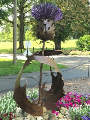 """The Earth, Wind and Flowers Garden Club members who attended the recent """"mystery trip"""" saw this enormous version of a thistle by artist Joe Ott. It is one of many sculptures on the grounds of Stan Hywet Gardens in Akron until October."""