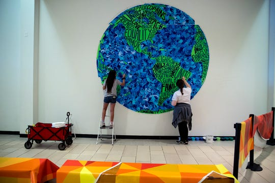 """Sierra Reyes, left, 12, and Danielle Resendez a participant in the K Space Contemporary Summer Mural Art Program La Palmera mall location, paints a section of the mural """"Peace, Love and Unity"""" for the mural that is located at the mall on July 31, 2019. In addition to creating lasting art, students participating in the two mural camps learn teamwork and problem solving skills."""