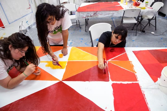 """Iliana Gandara, from left, 13, Faith Casas, 13, and Jocelyn Castillo, 15, participants in the K Space Contemporary Summer Mural Art Program La Palmera mall location, paints a section of the mural """"Peace, Love and Unity"""" for the mural that is located at the mall on July 30, 2019. In addition to creating lasting art, students participating in the two mural camps learn teamwork and problem solving skills."""