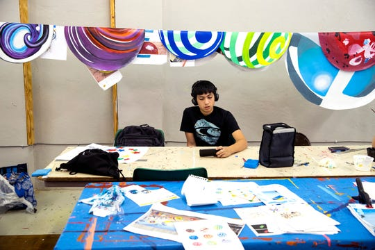 Marbles for a mural to be installed on the exterior of K Space Contemporary hang behind John Rios, 14, as he takes a break from the gallery's Summer Mural Art Program on July 26, 2019. The program's five-week mural camp has created seven murals over the last three years.