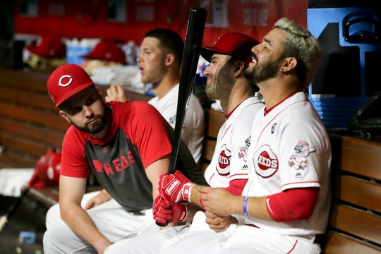 Cincinnati Reds left fielder Jesse Winker (33), first baseman Joey Votto (19) and third baseman Eugenio Suarez (7) share a laugh in the dugout in the sixth inning of an MLB baseball game, Monday, Aug. 5, 2019, at Great American Ball Park in Cincinnati.