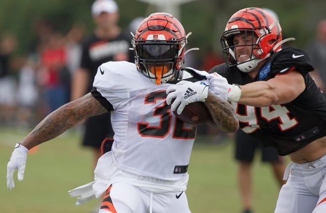 Cincinnati Bengals defensive end Sam Hubbard (94) tackles Cincinnati Bengals running back Trayveon Williams (32) during Bengals training camp on Aug. 6, 2019, in Cincinnati.