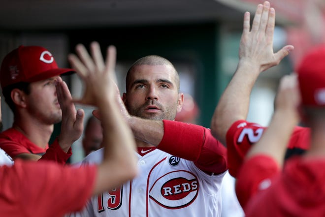 Cincinnati Reds first baseman Joey Votto (19) is congratulated in the dugout after scoring a run in the first inning of an MLB baseball game against the Los Angeles Angels, Monday, Aug. 5, 2019, at Great American Ball Park in Cincinnati.