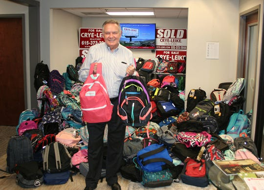 Harold Crye in front of 494 donated backpacks for Youth Villages.