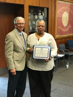 State Employment and Training Commission Chairman Dennis M. Bone presents Greater Raritan WDB Business and Financial Manager Saundra Addison‐Britto  with a certification document.