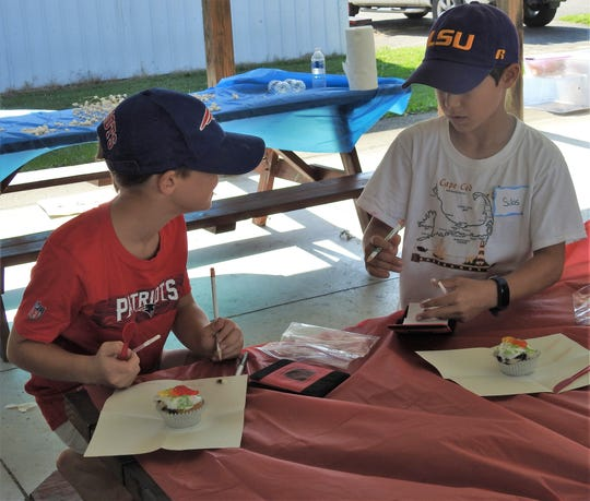 Colton Mathias and Silas Crothers, both 9, use straws to remove the interior of a cupcake to examine what is inside like a mock core sample during a 4-H science camp this week at the Coshocton County Fairgrounds.