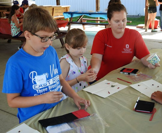 Isiah Kasper, 8, and Ciara Smith, 11, with help from Jenny Stricker of OSU Extension of Coshocton County, do a core sampling experiment with a cupcake and gelatin at a 4-H science camp earlier this week at the Coshocton County Fairgrounds