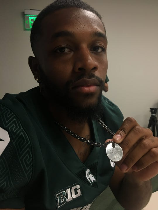 Michigan State senior cornerbabck Josh Butler shows his father's crematory tag that he wears on a chain around his neck. Steven Butler died in 2017, and Butler's mother Ladidra Bagley died April 28.