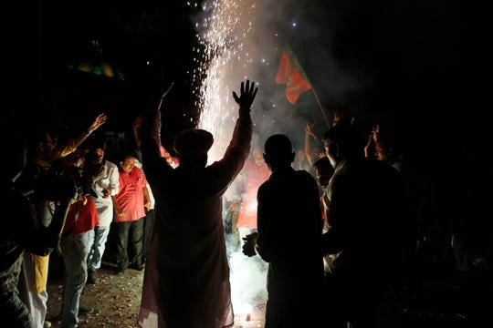 Supporters of India's ruling Bharatiya Janata Party (BJP) light firecrackers and celebrate the government revoking Kashmir's special status, in Lucknow, India, Tuesday, Aug. 6, 2019.