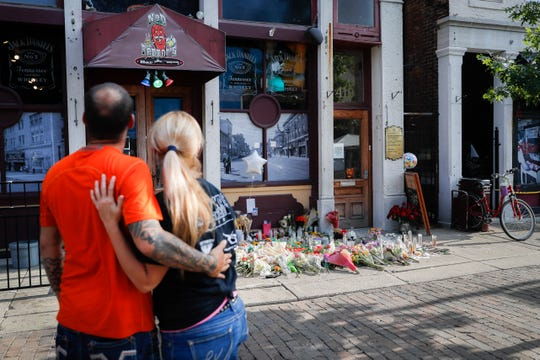 Mourners pause at a makeshift memorial for the slain and injured outside Ned Peppers bar in the Oregon District Tuesday, Aug. 6, 2019, in Dayton.