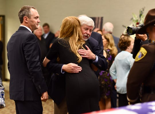 Former Michigan Governor Rick Snyder hugs Mary Warner, daughter of L. Brooks Patterson, during a  visitation for the late Oakland County Executive Tuesday.