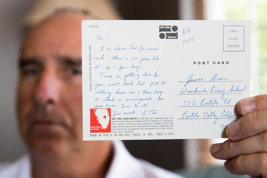 James Grein, 61, at his house in Sterling, Va., Friday, July 26, 2019, holds a Florida postcard sent to him when he was 15 years old by now-defrocked Cardinal Theodore McCarrick.