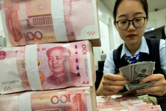 A bank employee counts U.S. dollar banknotes next to stack of 100 Chinese yuan notes at a bank outlet in Hai'an in eastern China's Jiangsu province, Tuesday, Aug. 6, 2019.
