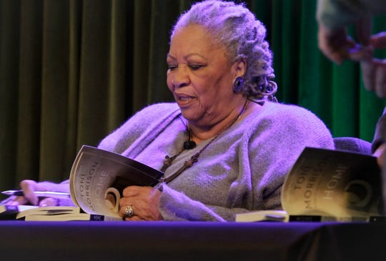 "In this Feb. 27, 2013 file photo, author Toni Morrison signs copies of her latest book ""Home,"" during Google's online program series, Authors At Google, in New York."