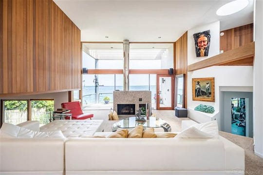 Family room with fireplace, large windows and contemporary paneling.