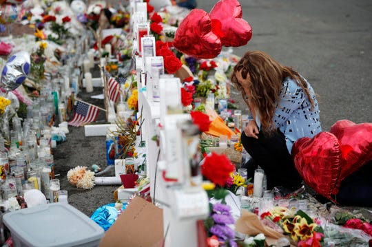 Gloria Garces kneels in front of crosses at a makeshift memorial near the scene of a mass shooting at a shopping complex, Tuesday, Aug. 6, 2019, in El Paso, Texas. The border city, jolted by a weekend massacre at a Walmart, absorbed more grief Monday as the death toll climbed and prepared for a visit from President Donald Trump over anger from El Paso residents and local Democratic leaders who say he isn't welcome and should stay away.