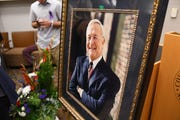 Photographs of former Oakland County Executive L. Brooks Patterson are seen during a public viewing.