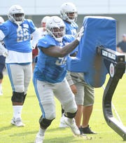 Lions defensive tackle P.J. Johnson comes off the sled during drills.