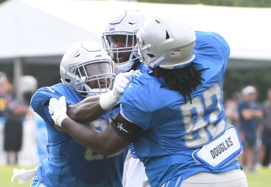 Lions defensive tackle Kevin Strong works against Darius Kilgo and P.J. Johnson during drills.