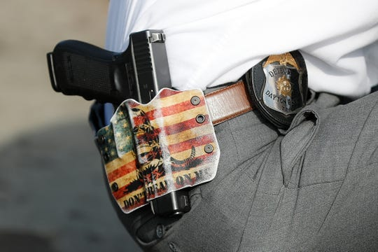 """A Dayton Police detective wears his sidearm in a holster bearing the phrase """"DON'T TREAD ON ME"""" as he performs a grid search beside a makeshift memorial for the slain and injured in the Oregon District after a mass shooting that occurred early Sunday morning, Tuesday, Aug. 6, 2019, in Dayton. Facing pressure to take action after the latest mass shooting in the U.S., Ohio's Republican governor urged the GOP-led state Legislature Tuesday to pass laws requiring background checks for nearly all gun sales and allowing courts to restrict firearms access for people perceived as threats."""