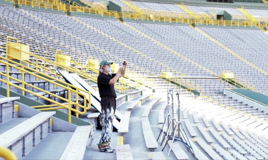 "Jeff Kahlow of Big Guy Hats, Fond du Lac, captures a snapshot for himself during a mid-July photo shoot at Lambeau Field for a Wisconsin Lottery Commercial he stars in, dressed  as ""Frozen Tundra Man."""