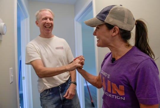 Worth Henley, left, a volunteer electrician and Kathleen Swinney of Dabo's All-In Team Foundation celebrate installing a thermostat during a Pickens County Habitat for Humanity work day for a family in Liberty Tuesday, August 6, 2019.