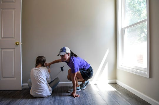 Kathleen Swinney, right, of Dabo's All-In Team Foundation talks with a daughter of the home recipient during a Pickens County Habitat for Humanity work day for a family in Liberty Tuesday, August 6, 2019.