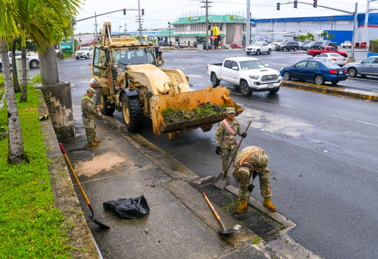 Soldiers of the Guam Army National Guard's 1224th Engineer Support Company clear a storm drain grate, near the intersection of Route 16 and Harmon Loop Road in Dededo, on Tuesday, Aug. 6, 2019. Acting on a directive by Gov. Lou Leon Guerrero, the engineering company, which was currently serving on annual training, was tasked with assiting the Department of Public Works in clearing of debris from storm water drains, curb inlets, catch basins, and roadways, according to the Governor's office.