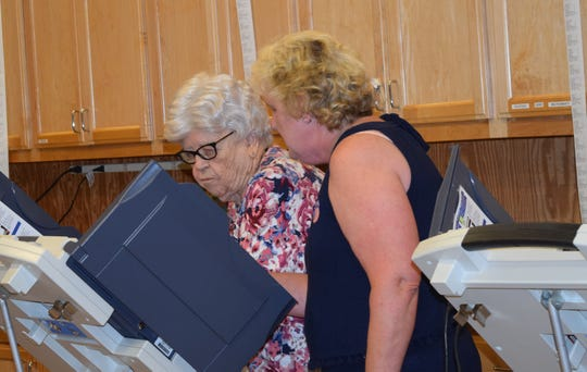 Marsha Tims, right, helps Mary Satterwhite cast her ballot Tuesday, Aug. 6, 2019, at Hattiesburg Zoo during Mississippi's primary elections.