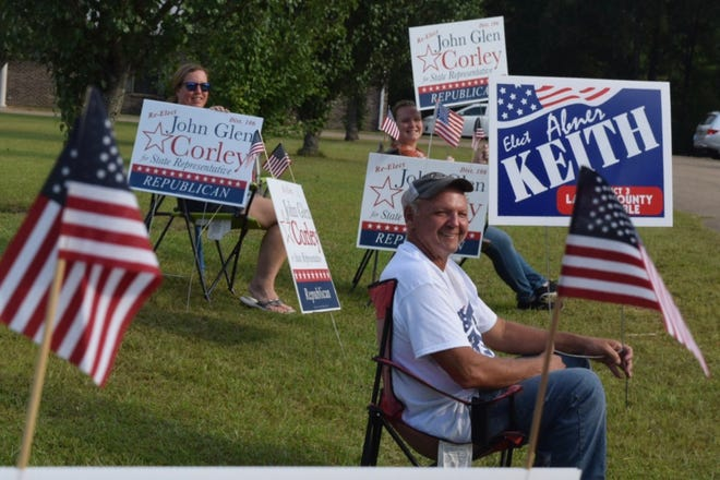 Campaigners greet voters in Lumberton during Mississippi's primary elections Tuesday, Aug. 6, 2019.