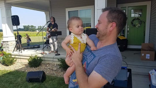 Nathan Klostermann of Coralville holds his niece, Iva Hougardy, while the baby's father Trevor performs during a recent Porchfest celebration.