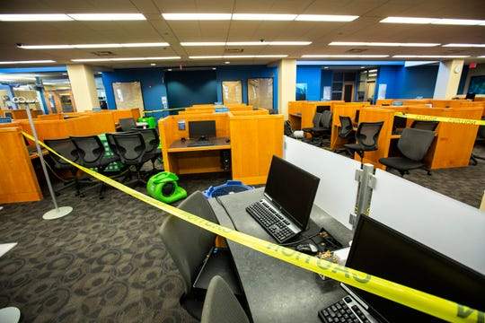 Yellow caution tape blocks off a section of computer stations while machines suck up water from a flooded restroom, Tuesday, Aug. 6, 2019, on the second floor at the Public Library in Iowa City, Iowa.