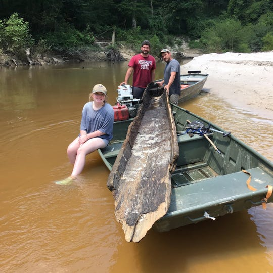 Brittany Spradley, 15, Jacob Livingston (center), and Tommy Elias take a break while removing a 300-year-old canoe from Tallahala creek that was found by Spradley's father, Vincent Spradley.