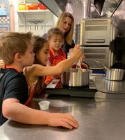 Britton Bates of Madison, age 8, left, watches Maris Walters of Madison, age 10, as she stirs sauce for ice cream. Also watching are Zoe Gibbs of Jackson, age 4, and Kelli Stout of Madison, cooking school director at the Everyday Gourmet in Ridgeland.