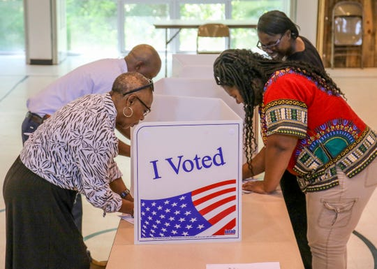 Wanda Lynch, left, Enrico Johnson, Diana Hopson and Dorothy Hopson make their selections as they vote Tuesday inside the family life center at Trinity Presbyterian Church in Meridian, Miss., Tuesday Aug. 6, 2019.