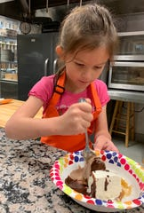 Ava Gibbs of Jackson, age 6, prepares to taste no-churn vanilla ice cream, no-churn chocolate ice cream, caramel sauce and chocolate sauce.