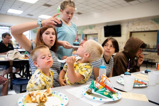 Isabella Humphrey gets a cupcake for her twin brothers, Jordan, left, and Jayce during New Life United Methodist's Dinner Church at East Knox County Elementary School on Tuesday, July 30, 2019. Also at the table are, from left, Summer Taylor, Mary Williams, and Frankie Raider.
