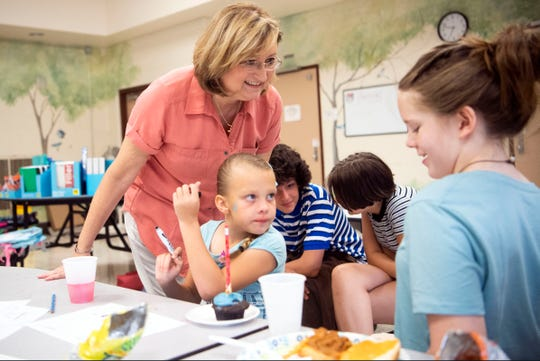 New Life minister the Rev. Teresa Atkins McClure meets with children during Dinner Church at East Knox County Elementary on Tuesday, July 30, 2019.