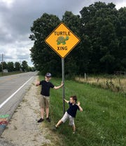 Jack Wietbrock, left, and his brother, Teddy, stopped to get a picture with one of West Lafayette's new 'Turtle Xing' signs on Cherry Lane on Tuesday, Aug. 6, 2019. The signs went up after Jack wrote a letter to West Lafayette Mayor John Dennis, asking for help for turtles getting run over by cars on the city's roads.