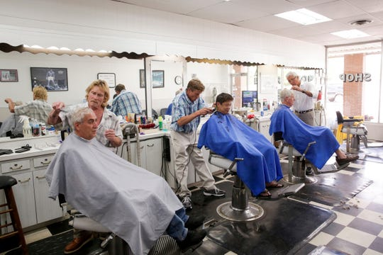 Barbers, from left, Joe Lanie Jr., Larry Burton Jr. and Larry Burton Sr. cut customers hair, Tuesday, Aug. 6, 2019 at Lanie's Barber Shop in West Lafayette. Joe Lanie Sr. and Larry Burton Sr. opened the barbershop in 1969 across the street from their current location, 455 Sagamore Parkway W. which they have occupied ever since, now running the business with their children.